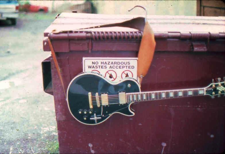 (9) Guitar slung over dumpster